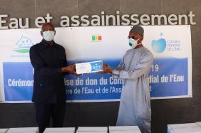 Mr. Mamadou DIA (right), Governor of the World Water Council representing President Loïc Fauchon, hands over a batch of soap to Mr. Serigne Mbaye Thiam, Senegalese Ministry of Water and Sanitation, during the ceremony on April 24, 2020.